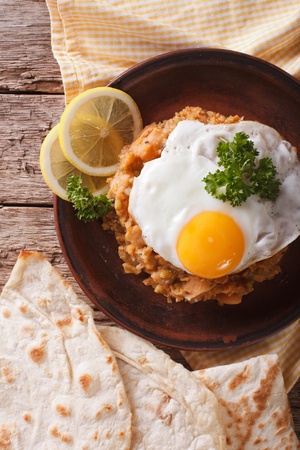 ful: ful medames with a fried egg and bread close-up on the table. vertical view from above Stock Photo