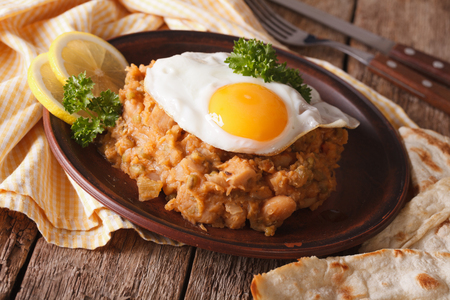 ful: ful medames with a fried egg and pita close up on the table. horizontal