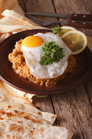 ful: Arabic Breakfast: ful medames with a fried egg on a plate close-up. Vertical Stock Photo