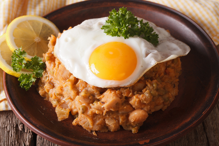ful: Arabic Breakfast: ful medames with a fried egg on a plate close-up. horizontal Stock Photo
