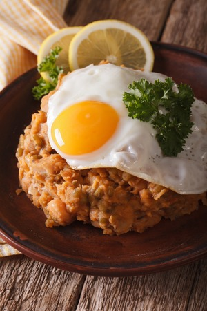 ful: Arabic cuisine: ful medames with a fried egg on a plate close-up. vertical Stock Photo