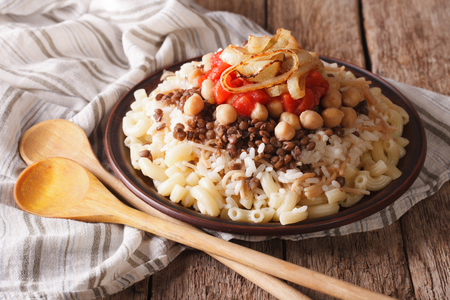 Arabic cuisine: kushari of rice, pasta, chickpeas and lentils close up on a plate on the table. horizontal Banque d'images
