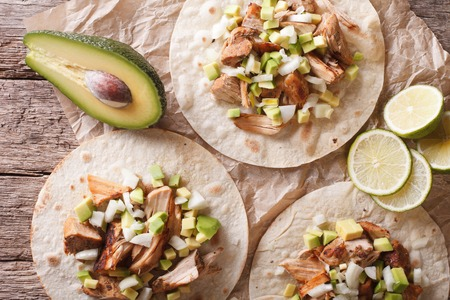 Mexican food: tortilla with carnitas, onions and avocado close-up on the table. horizontal top view Stock Photo