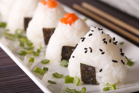 Japanese food onigiri rice balls macro on a white plate. horizontal