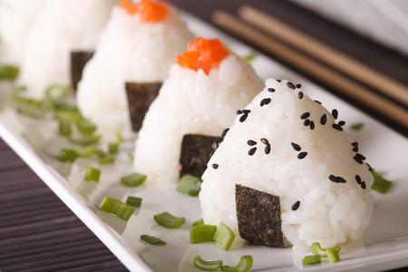 Japanse voedsel onigiri rijst ballen macro op een witte plaat. horizontaal