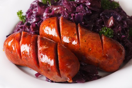 red braised: braised red cabbage and grilled sausages closeup on a plate. horizontal