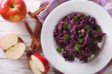 red braised: braised red cabbage with apples close up on a plate. Horizontal view from above