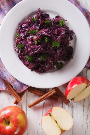 red braised: braised red cabbage with apples close up on a plate. vertical view from above