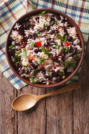 Rice with red beans and vegetables in a bowl on the table. vertical view from above
