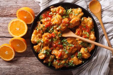 oranje kip in zoetzure saus op een plaat close-up op de tafel. horizontale weergave van bovenaf