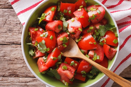 tomate ensalada: Delicious fresh tomato salad with onion in a bowl close-up. Horizontal view from above