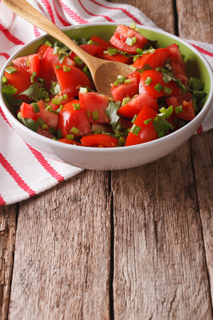 tomate ensalada: Homemade fresh tomato salad with herbs close up in a bowl on the table. vertical