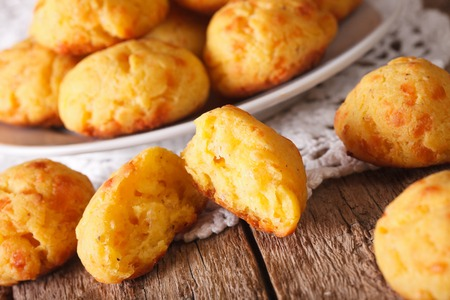 choux bun: Freshly baked gougere buns with cheese close-up on the table. horizontal, rustic