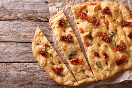 Sliced bread Italian focaccia with sun-dried tomatoes and rosemary on the table. horizontal view from above Banque d'images
