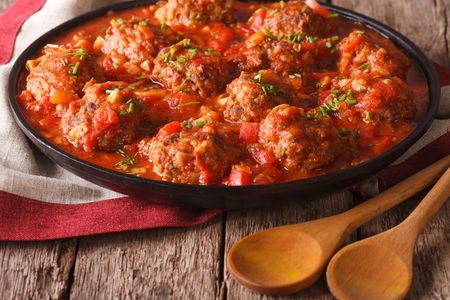 Tasty meatballs with spicy tomato sauce on a dish on the table close-up. horizontal