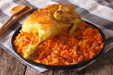 Traditional Arabic food: kabsa with chicken and almonds close-up on a plate. Horizontal