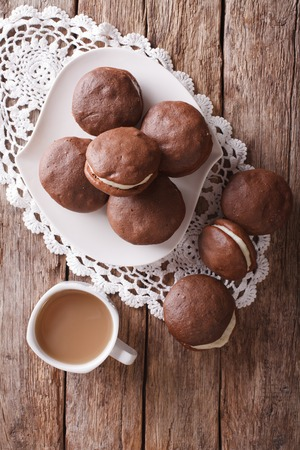 american dessert: American Whoopie pie dessert and coffee on the table. vertical view from above Stock Photo