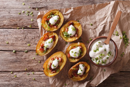 Rustic potato skins with cheese, bacon and sour cream on the table. horizontal view from above Фото со стока