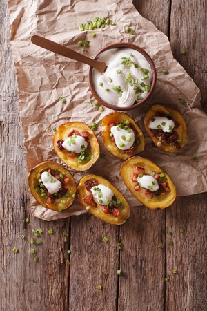 skins: Rustic potato skins with cheese, bacon and sour cream on the table. vertical view from above Stock Photo