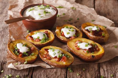 batata: pieles de patatas r�sticas con queso, tocino y crema agria primer plano sobre la mesa. horizontal