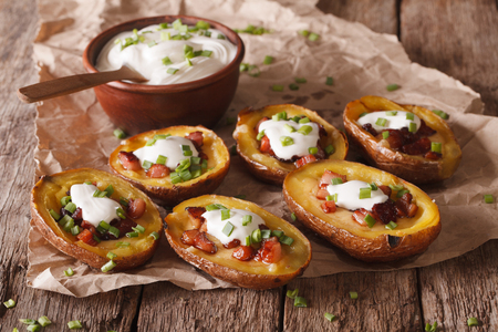 Rustic potato skins with cheese, bacon and sour cream close-up on the table. horizontal