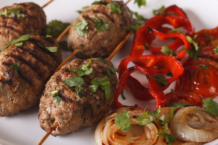 kabab: Turkish kofte kebab with grilled vegetables on a plate close-up. horizontal