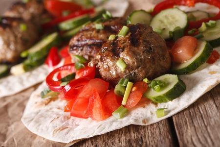 ensalada tomate: Albóndigas con verduras frescas en una tortilla en primer plano en la tabla. horizontal