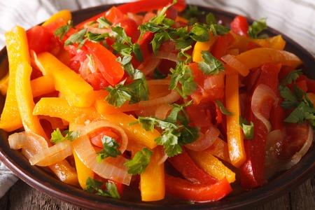 peperoni in umido con pomodori e cipolle da vicino su un piatto. orizzontale