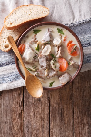 convivial: Beef with mushrooms in cream sauce in a bowl on the table. Vertical view from above Stock Photo