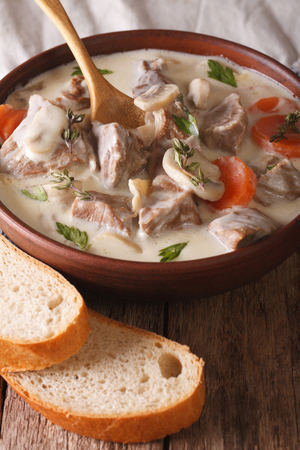 convivial: Veal with mushrooms in cream sauce in a bowl on the table. Vertical