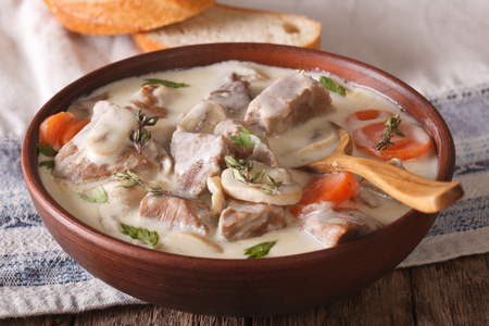 convivial: Veal with mushrooms in cream sauce in a bowl on the table. horizontal