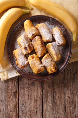 platanos fritos: Fried bananas in batter on a plate on the table. Vertical view from above