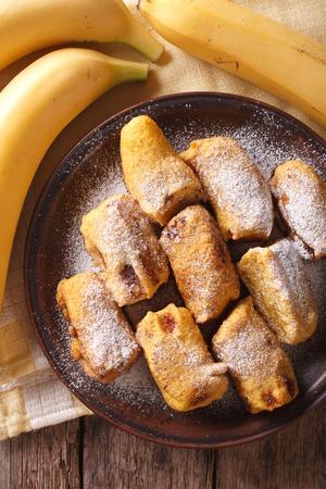 platanos fritos: Plátanos fritos rebozados en un primer plato en la mesa. Vista vertical desde arriba Foto de archivo