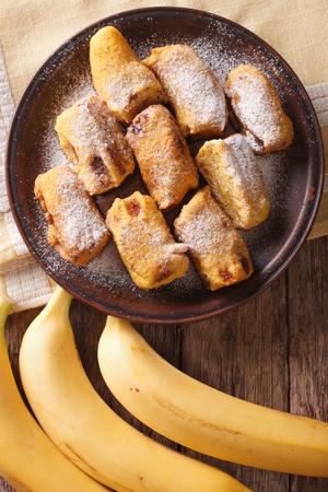 platanos fritos: Pisang goreng plátanos fritos rebozados en un primer plato en la mesa. Vista vertical desde arriba