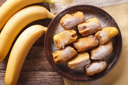platanos fritos: Pisang goreng plátanos fritos rebozados en un primer plato en la mesa. Vista horizontal desde arriba