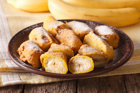 platanos fritos: Traditional fried bananas sprinkled with powdered sugar close-up on the table. horizontal