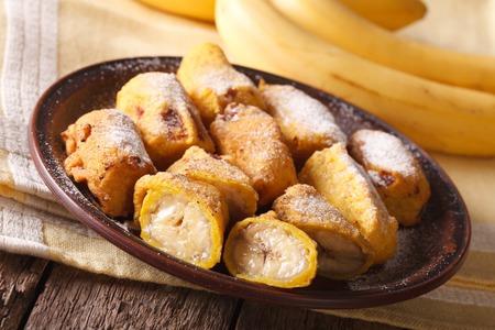 platanos fritos: plátanos fritos sabrosos rebozados espolvorean con azúcar en polvo en primer plano en la tabla. Horizontal