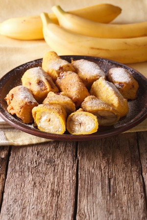 platanos fritos: Tasty fried bananas in batter sprinkled with powdered sugar close-up on the table. vertical