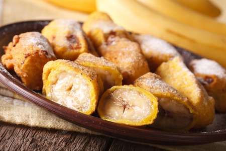 platanos fritos: Fried bananas in batter sprinkled with powdered sugar close-up on a plate on the table. horizontal