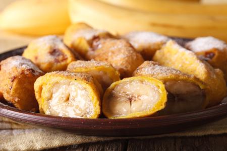 platanos fritos: Pisang goreng plátanos fritos rebozados en un primer plato en la mesa. Horizontal Foto de archivo