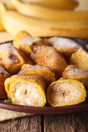 platanos fritos: Pisang goreng fried bananas in batter on a plate closeup on the table. vertical