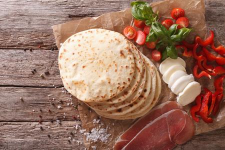 イタリアン ピアディーナ フラット パン、ハム、チーズ、野菜クローズ アップ テーブルの上。水平トップ ビュー 写真素材