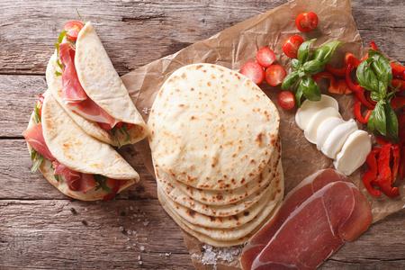 テーブルの上のハム、チーズ、野菜のクローズ アップとイタリアン ピアディーナ。上から水平ビュー