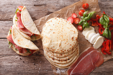 Italian piadina with ham, cheese and vegetables close-up on the table. Horizontal view from above Standard-Bild