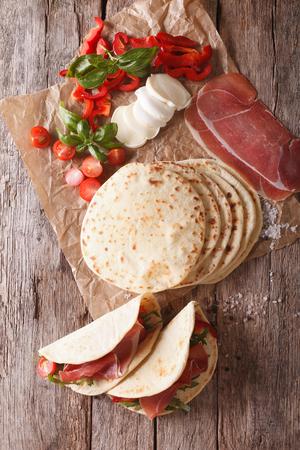 テーブルの上のハム、チーズ、野菜のクローズ アップとイタリアン ピアディーナ。上から垂直ビュー
