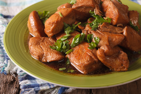 Delicious Filipino Food: Adobo chicken with herbs close-up on a plate on the table. horizontal