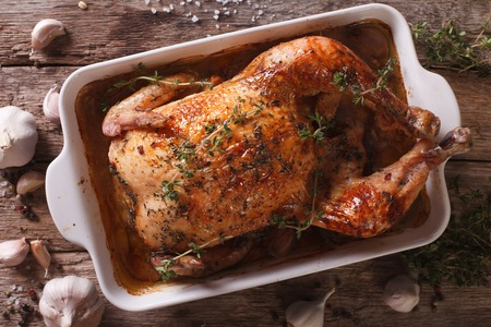 Baked Chicken with forty cloves of garlic and ingredients close-up on the table. horizontal view from above Stock fotó