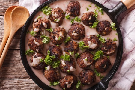 Swedish meatballs kottbullar with lingonberry sauce closeup on a frying pan. horizontal view from above