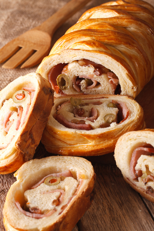 filled: sliced bread stuffed with ham and olives close-up on the table. vertical