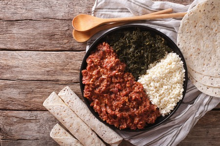 ethiopian: Ethiopian kitfo with herbs and cheese ayibe on a plate close-up. horizontal view from above